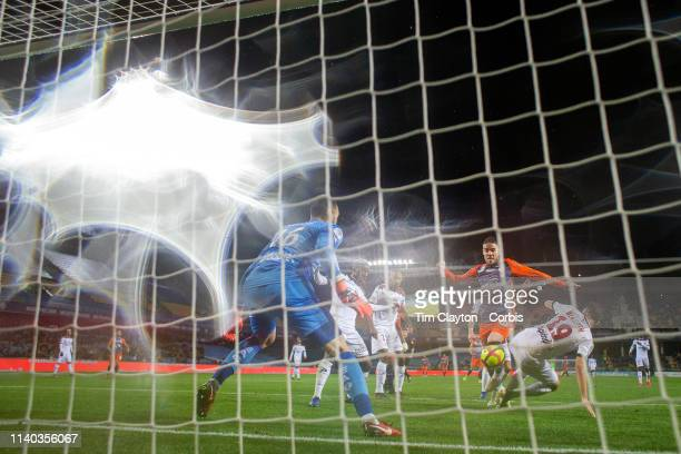 Mihailo Ristic of Montpellier beats defender Mehdi Merghem of Guingamp and goalkeeper MarcAurele Caillard of Guingamp to score his sides second goal...