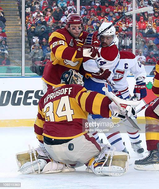 Miikka Kiprusoff and Robyn Regehr of the Calgary Flames defend the net against Brian Gionta of the Montreal Canadiens during the 2011 NHL Heritage...