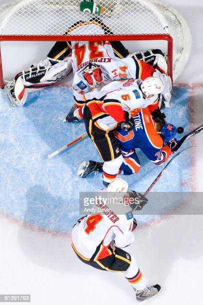 Miikka Kiprusoff Mark Giordano and Jay Bouwmeester of the Calgary Flames defend against an opposite Ryan Stone of the Edmonton Oilers on October 3...