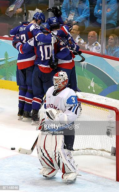 Miikka Kiprusoff of Finland looks on as Marian Hossa of Slovakia celebrates his second period goal with his team during the ice hockey men's bronze...