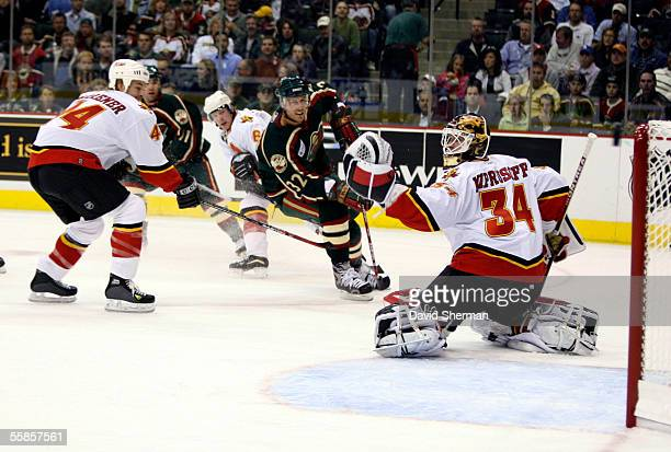 Miikka Kiprusoff of the Calgary Flames catches the shot by Marc Chouinard of the Minnesota Wild during their season opening game on October 5, 2005...