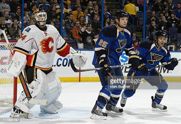 Miikka Kiprusoff of the Calgary Flames defends against Chris Stewart and Andy McDonald of the St Louis Blues in an NHL game on April 1 2011 at...