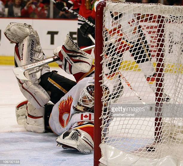 Miikka Kiprusoff of the Calgary Flames dives to try and stop the puck on a goal by Jonathan Toews of the Chicago Blackhawks at the United Center on...