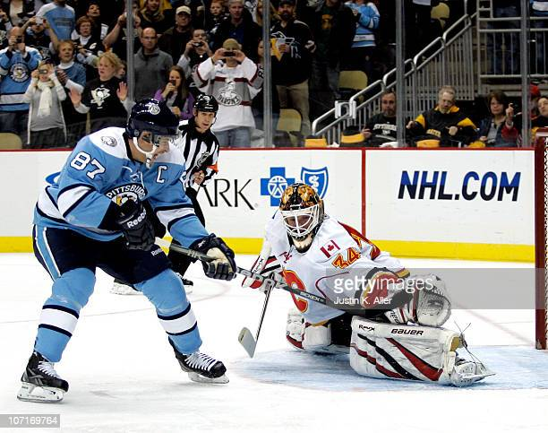 Miikka Kiprusoff of the Calgary Flames makes a glove save on Sidney Crosby of the Pittsburgh Penguins on a penalty shot at Consol Energy Center on...