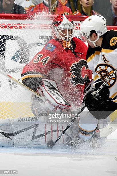 Miikka Kiprusoff of the Calgary Flames makes a save against Patrice Bergeron of the Boston Bruins on October 30 2008 at Pengrowth Saddledome in...