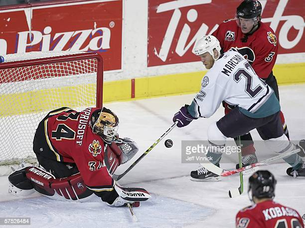 Miikka Kiprusoff of the Calgary Flames makes a save against Todd Marchant of the Anaheim Mighty Ducks as Dion Phaneuf tries to defend during the...