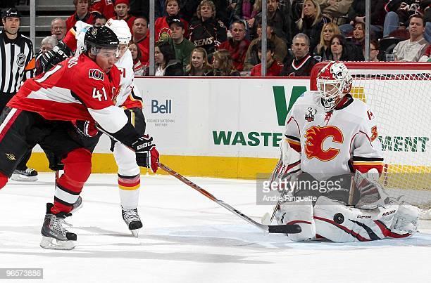 Miikka Kiprusoff of the Calgary Flames makes a save on a shot by Jonathan Cheechoo of the Ottawa Senators at Scotiabank Place on February 9 2010 in...