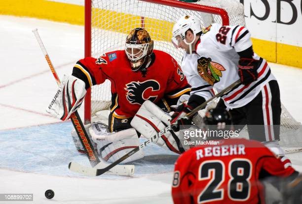 Miikka Kiprusoff of the Calgary Flames makes a save on Troy Brouwer of the Chicago Black Hawks in third period action at Scotiabank Saddledome...