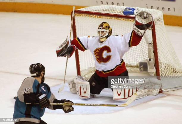 Miikka Kiprusoff of the Calgary Flames protects the net from Patrick Marleau of the San Jose Sharks in Game five of the 2004 NHL Western Conference...