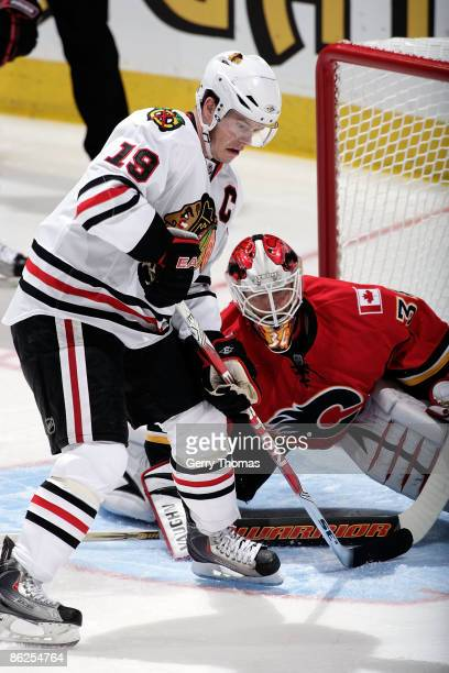 Miikka Kiprusoff of the Calgary Flames puts his paddle on the ice while Jonathan Toews of the Chicago Blackhawks skates in front of the net during...
