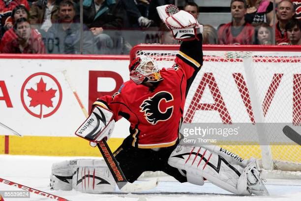 Miikka Kiprusoff of the Calgary Flames reaches for the puck to make a glove save against the St. Louis Blues on March 20, 2009 at Pengrowth...