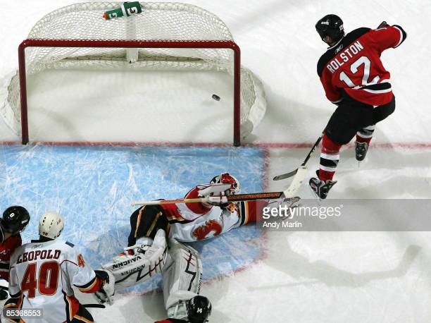 Miikka Kiprusoff of the Calgary Flames sprawls but can't stop a goal by Brian Rolston of the New Jersey Devils at the Prudential Center on March 10...