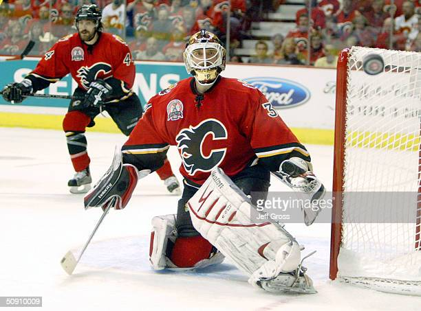 Miikka Kiprusoff of the Calgary Flames watches the puck skip through to the boards against the Tampa Bay Lightning in game three of the NHL Stanley...