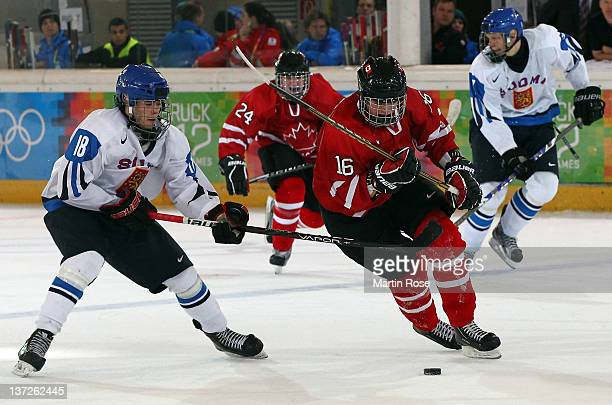 Miikka Pitkanen of Finland and Reid Duke of Canada battle for the puck during the men's preliminary round ice hockey match between Finland and Canada...