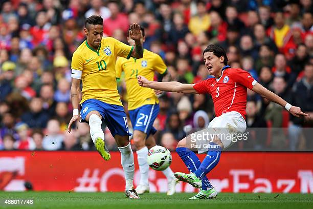 Miiko Albornoz of Chile clears the ball as Neymar of Brazil closes in during the international friendly match between Brazil and Chile at the...