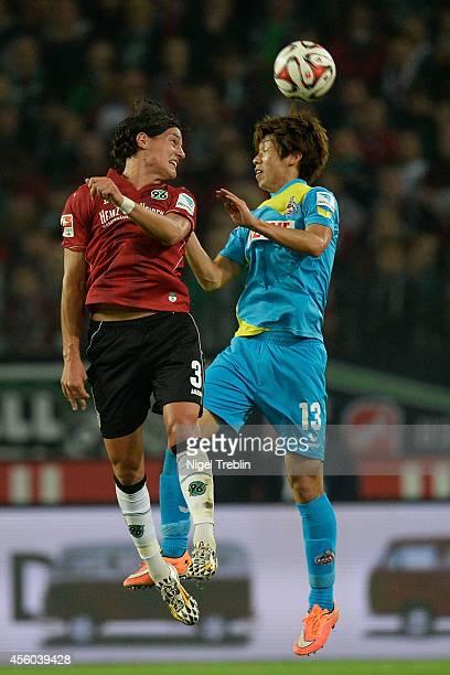 Miiko Albornoz of Hannover and Yuya Osako of Koeln compete for the ball during the Bundesliga match between Hannover 96 and 1. FC Koeln at HDI-Arena...