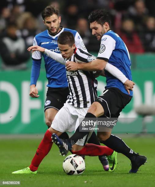 Mijat Gacinovic Of Frankfurt Is challenged by Christopher Noethe and Stephan Salger of Bielefeldduring the DFB Cup quarter final between Eintracht...