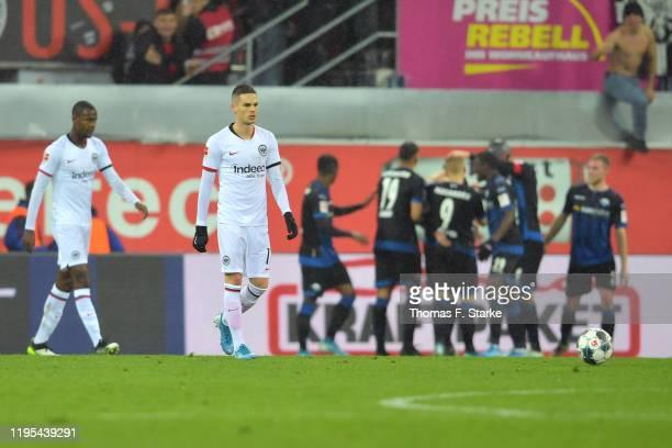 Mijat Gaćinovic of Eintracht Frankfurt looks dejected as Sebastian Schonlau of SC Paderborn 07 celebrates with teammates after scoring his sides...
