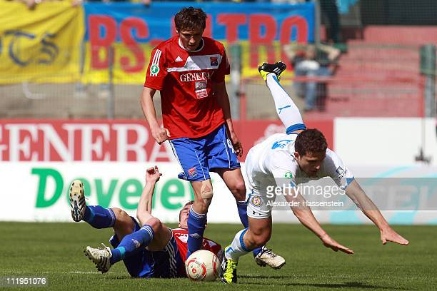 Mijo Tunjic of Unterhaching and his team mate Sebastian Mittlerhuber battles for the ball with Ken Reichel of Braunschweig during the Third League...