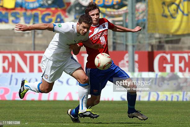 Mijo Tunjic of Unterhaching battles for the ball with Ken Reichel of Braunschweig during the Third League match between SpVgg Unterhaching and...
