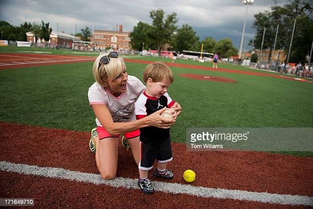 Mika Brzezinski of MSNBC plays with Jonah Frank King son of CNN's Dana Bash before the Congressional Women's Softball game that pits Congresswomen...