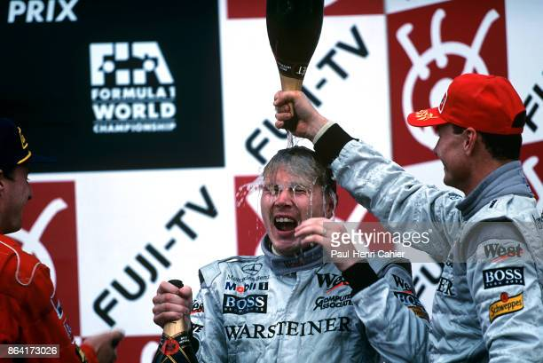 Mika Hakkinen, David Coultard, Eddie Irvine, Grand Prix of Japan, Suzuka Circuit, 01 November 1998. David Coultard pours champagne over the head of...