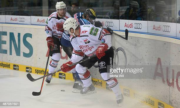 Mika Hannula and Marcel Mueller of Koeln battle with Tim Conboy of Ingolstadt for the puck in game six of the DEL final playoffs between ERC...