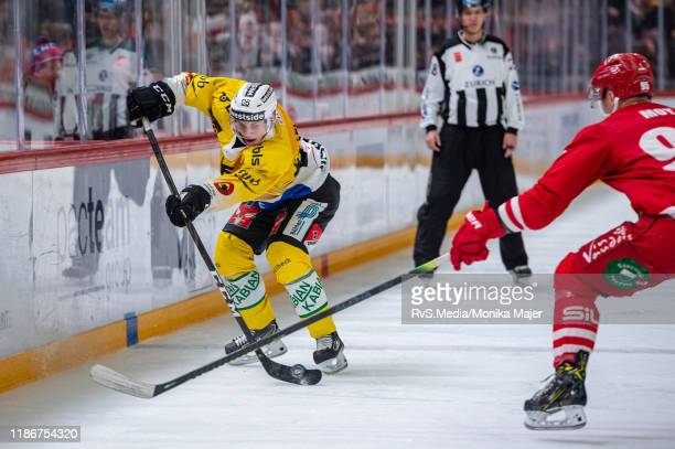Mika Henauer of SC Bern battles for the puck with Tyler Moy of Lausanne HC during the Swiss National League game between Lausanne HC and SC Bern at...
