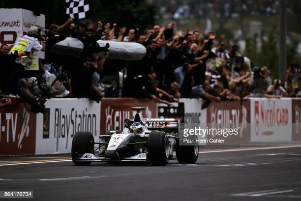 Mika Häkkinen, McLaren-Mercedes MP4/14, Grand Prix of Japan, Suzuka Circuit, 31 October 1999. Mika Häkkinen waves as he crosses the finish line to...