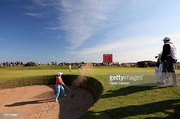 Mika Miyazato of Japan hits from a bunker on the 15th hole during the third round of the 2011 Ricoh Women's British Open at Carnoustie on July 30...