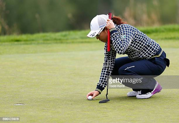 Mika Miyazato of Japan places her ball on the 11th green during the third round of the Canadian Pacific Women's Open at Priddis Greens Golf and...