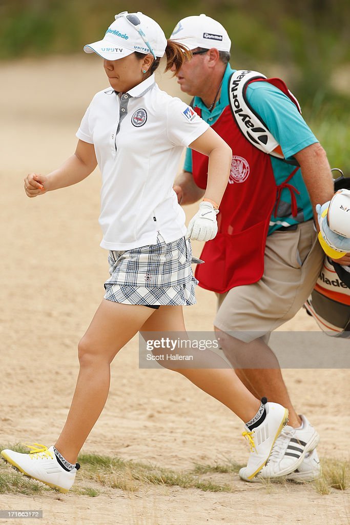 Mika Miyazato of Japan runs with her caddie Chad Payne on the 13th hole during the first round of the 2013 U.S. Women's Open at Sebonack Golf Club on June 27, 2013 in Southampton, New York.
