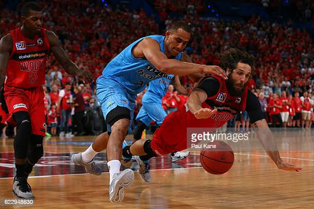 Mika Vukona of the Breakers and Matt Knight of the Wildcats chase a loose ball during the round six NBL match between the Perth Wildcats and the New...