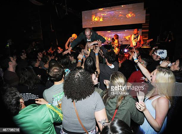 Mika Yoshimura of BoPeep and PeelanderPurple of PeelanderZ watch as audience members stage dive at Live Wire on March 26 2015 in Athens Georgia