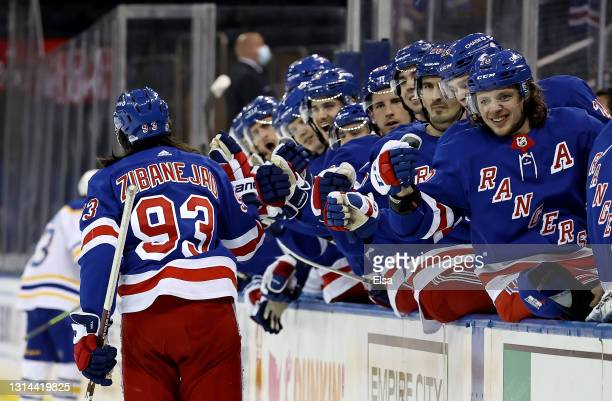 Mika Zibanejad of the New York Rangers is congratulated by Artemi Panarin and the rest of the bench after Zibanejad scored a hat trick in the second...
