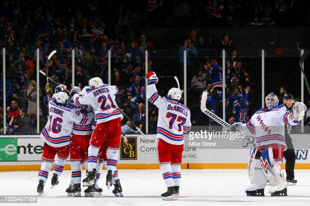 Mika Zibanejad of the New York Rangers is congratulated by his teammates after scoring the game-winning goal against the New York Islanders during...
