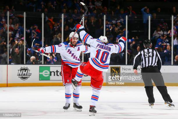 Mika Zibanejad of the New York Rangers is congratulated by his teammate Artemi Panarin after scoring the game-winning goal against the New York...