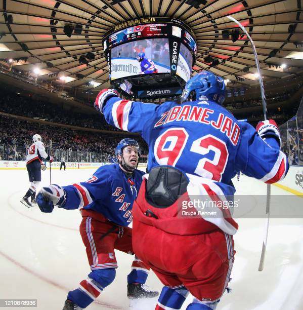 Mika Zibanejad of the New York Rangers scores his fifth goal of the game in overtime defeat the Washington Capitals 5-4 and is joined by Tony...