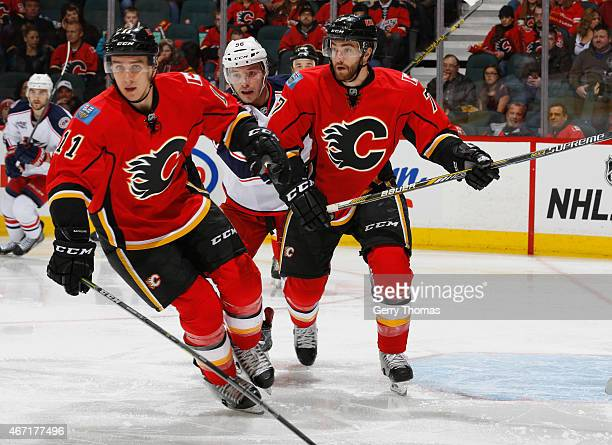Mikael Backlund and TJ Brodie of the Calgary Flames hunt down the puck against the Columbus Blue Jackets at Scotiabank Saddledome on March 21 2015 in...