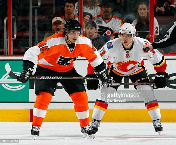Mikael Backlund of the Calgary Flames and Danny Briere of the Philadelphia Flyers exchange words as they wait for a faceoff during a hockey game at...