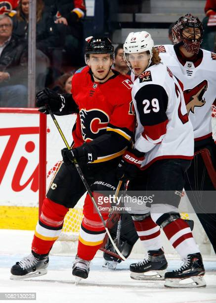 Mikael Backlund of the Calgary Flames and Mario Kempe of the Arizona Coyotes compete for position during an NHL game on January 13 2019 at the...