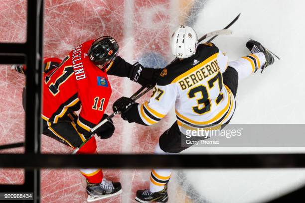 Mikael Backlund of the Calgary Flames and Patrice Bergeron of the Boston Bruins battle for position in an NHL game on February 19 2018 at the...
