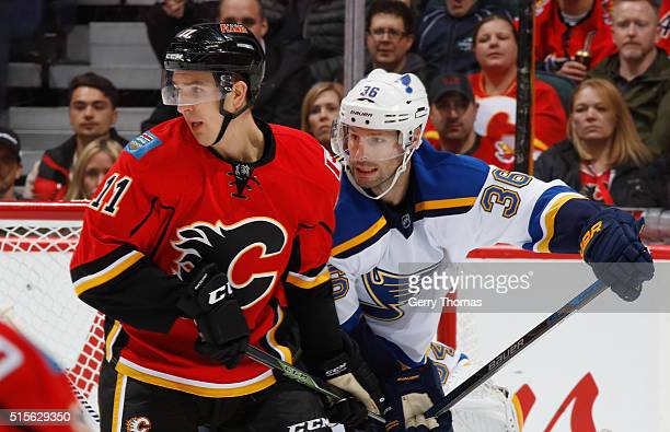 Mikael Backlund of the Calgary Flames battles against Troy Brouwer of the St Louis Blues at Scotiabank Saddledome on March 14 2016 in Calgary Alberta...