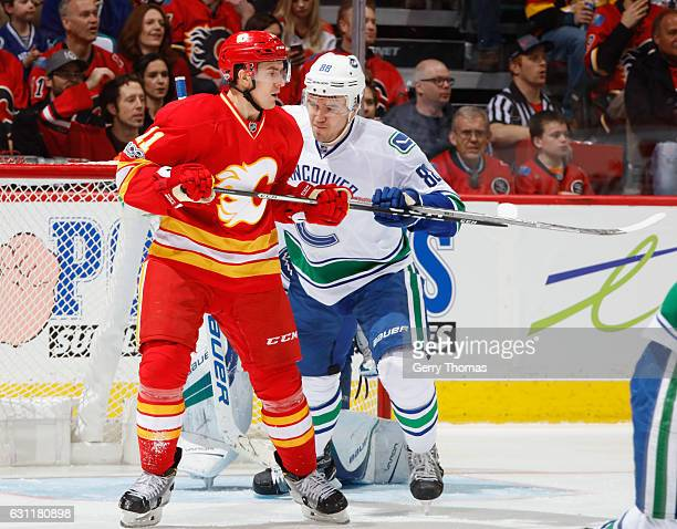 Mikael Backlund of the Calgary Flames battles in front against Nikita Tryamkin of the Vancouver Canucks at Scotiabank Saddledome on January 7 2017 in...