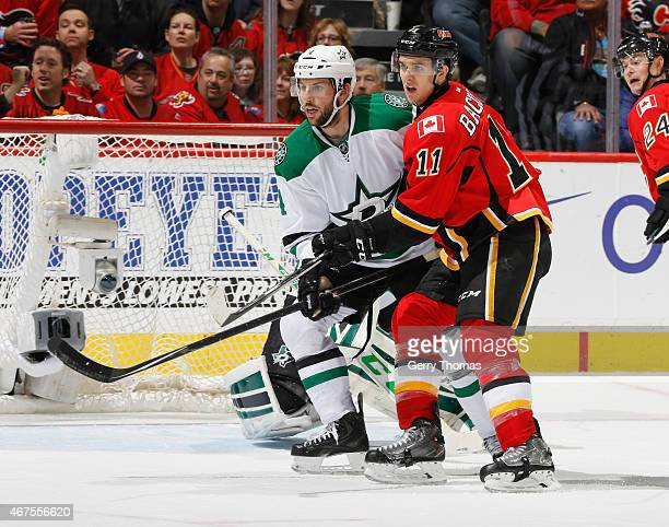 Mikael Backlund of the Calgary Flames battles in front of the net against Jason Demers of the Dallas Stars at Scotiabank Saddledome on March 25 2015...