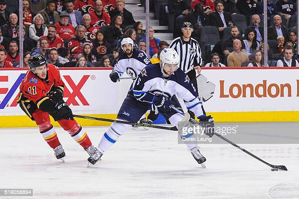 Mikael Backlund of the Calgary Flames checks Alexander Burmistrov of the Winnipeg Jets during an NHL game at Scotiabank Saddledome on March 16 2016...