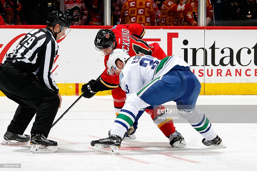 Mikael Backlund #11 of the Calgary Flames faces off against Henrik Sedin #33 of the Vancouver Canucks during an NHL game on December 23, 2016 at the Scotiabank Saddledome in Calgary, Alberta, Canada.