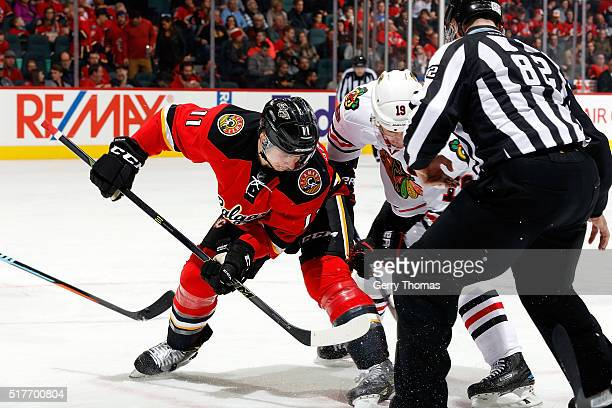 Mikael Backlund of the Calgary Flames faces off against Jonathan Toews of the Chicago Blackhawks during an NHL game at Scotiabank Saddledome on March...