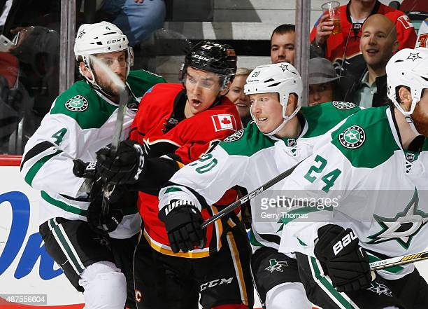 Mikael Backlund of the Calgary Flames gets crunched between Jason Demers and Cody Eakin of the Dallas Stars at Scotiabank Saddledome on March 25 2015...