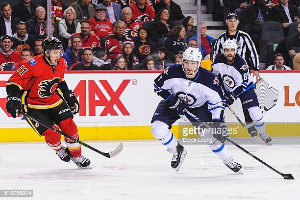 Mikael Backlund of the Calgary Flames looks to check Alexander Burmistrov of the Winnipeg Jets during an NHL game at Scotiabank Saddledome on March...